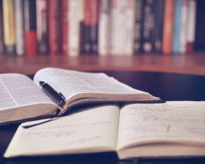 libros abiertos con lapicera, y estantería de fondo